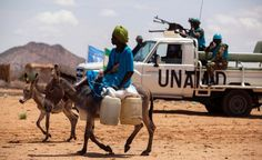 FILE - A man rides his donkey past Tanzanian UNAMID troops standing guard at a camp for internally displaced people (IDP) in Khor Abeche, South Darfur, Sudan. United Nations Peacekeeping, Uniform Insignia, Fiji, Troops, Military Vehicles, Camel, Arms, Meet, Japan