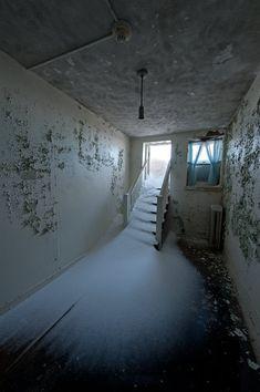 Blowing snow enters the abandoned J.N. Adams Memorial Hospital through an open, hallway door. Perrysburg, NY