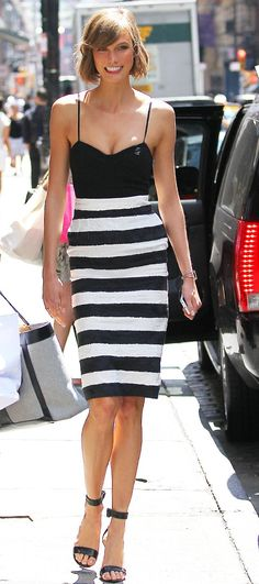 Kloss showed off her style stripes in New York City with a Black Bustier and a body-hugging Black-and-White striped Skirt. A solo cuff and ankle strap heels completed her Street Style Look.