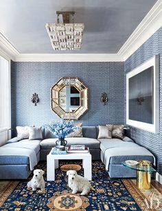 In the family room of a Chicago penthouse by Michael S. Smith Inc., the walls are sheathed in a John Robshaw fabric that matches perfectly with the wraparound blue sofa.