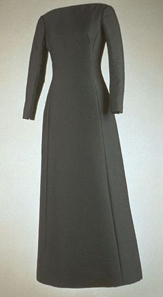 Black Alaskine and silk taffeta gown, by Oleg Cassini, American, 1962. Worn by Jacqueline Kennedy for her audience with Pope John XXIII at the Vatican on March 11, 1962. Her selection of stiff, unyielding fabrics such as this silk and wool blend called Alaskine, lends an armorial quality to much of her clothing from this period.