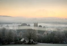 Fog lingers around the church spire of St Peter and St Paul as the sun rises over the village of Kilmersdon near Radstock in Somerset