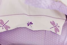 Dragonflies embroidered onto crisp white pillowcases echo the playful sweep of butterflies floating above the bed.