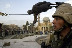 Iraqi civilians and U.S. soldiers pull down a statue of Saddam Hussein in downtown Baghdad,on April 9 2003