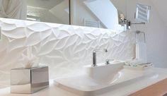 Sobre et élégante, cette salle de bains design blanche nous séduit par sa faïence matiérée, sa vasque épurée signée des designers Erwan et Ronan Bouroullec et son miroir rétroéclairé tendance. Découverte d'une petite salle de bains design qui en met plein les mirettes !