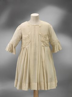 Girls party dress, of cream-coloured silk lined with cotton, trimmed with embroidery at the waist. c. 1890.