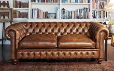 The Chesterfield sofa, typified by its familiar design - a large couch with rolled arms the same height as the back, with deep button tufting and nail-head trim. The lore around the Chesterfield is that it was invented when the fourth Earl of Chesterfield Chesterfield Sofas, Leather Sectional Sofas, Chesterfield Library, Chesterfield Living Room, Leather Furniture, Home Furniture, Antique Furniture, Office Furniture, Vintage Leather Sofa