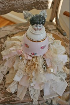 OK think of this as less kitschy than the teacup fairy thing, but the vintage lace, ribbon and fabric skirt would make an excellent base for a princess doll to go along with the princess theme for one of our future daughters :-)