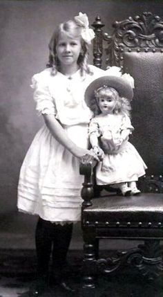 Vintage photo of young girl with her doll, circa 1915.