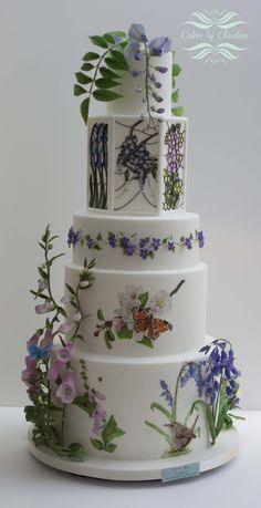 "Squires Kitchen Exhibition 2016. My Gold award winner and first place in the ""Stunning sugar paste: Tiered wedding cake"" class #woodland #cake #country #wedding #birds #butterfiy #sugar flowers #violets #primroses #foxgloves #bluebells #wren #robin #wisteria"