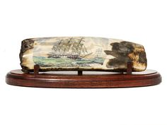 """""""Old Ironsides Races into Battle"""" Color scrimshaw on ancient walrus tusk ivory artifact by Chris Lehwalder. Marvelous rendition of the most famous American warship, the U.S.S. Constitution. She is shown in blustery weather, with most of her sails up, racing to an upcoming battle. On the horizon can be seen another American warship. Size: 11""""W x 3 3/4""""D x 3 1/4""""H Price: $3,250.00 -- on ScrimshawGallery.com #scrimshaw"""