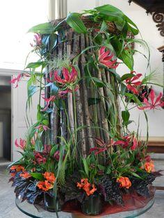 """De grassen staan voor de wind; de Geest daalde neer als het geluid van een hevige wind. De meerdere """"rood """"tinten verwijzen naar hoe Gods vurige inspiratie verschillende wegen met ons mensen gaat. Onderaan de schikking zijn bloemen gestoken in 7 bloemstukjes. Het getal 7 duidt op de 7 gaven van de Heilige Geest. Floral Arrangements, Floral Design, Plants, Inspiration, Biblical Inspiration, Floral Patterns, Flora, Flower Arrangement, Wreaths"""