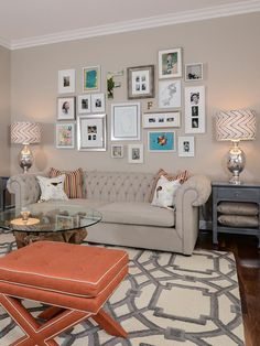 A bright coral-colored X-bench dresses up this living room. A trellis-patterned area rug defines the sitting area, which also includes a lig...