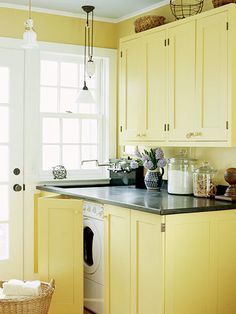 Make the laundry room disappear! Custom-built yellow cabinetry conceals these appliances.