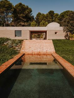 Tiled steps lead down from the terrace to the pool of Casa Ter, a concrete and stone house designed by architecture studio Mesura in Baix Empordà, Spain.