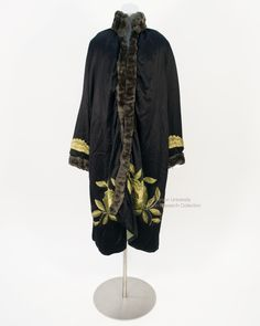 Black satin crepe long sleeved coat, with large embroidered roses in bright green thick silk around hem, scalloped lime green embroidery on cuffs, blue-brown dyed mole fur on collar cuffs and opening. C. 1920s. FRC 2014.07.071