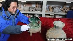Chinese archaeologists unearth 2,400-year-old soup: A Shaanxi Provincial Archeological Institute official displays the bronze vessel thought to contain the ancient soup.