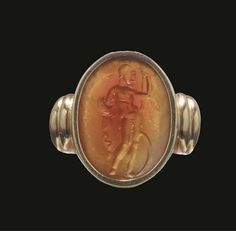 A ROMAN CORNELIAN INTAGLIO OF MARS   1ST CENTURY B.C.   The god standing with weight on his left leg, naked except for a crested helmet on his head, he leans on spear held in his left hand, a circular shield resting on the ground by his left leg, and holds a cloak wrapped around his right arm, in later ring setting