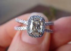 Cushion-cut colored diamond set in a split-shank, halo ring by Henri Daussi.