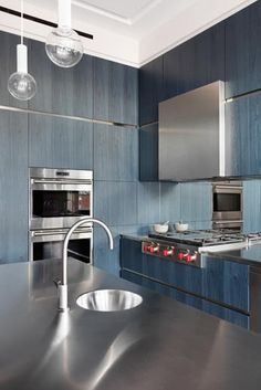 Kitchen in blue Bolivar veneer with brushed stainless steel worktops and tall solid timber glazed doors