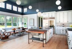 Cottage Kitchen with Flat panel cabinets, High ceiling, Complex marble counters, Farmhouse sink, Flush, Built In Refrigerator