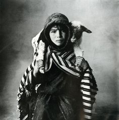 A young Berber shepherdess of the Aït Yazza people in the High Atlas, with a newborn lamb.