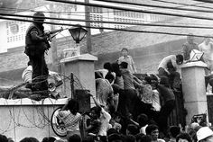 Mobs of Vietnamese people scale the wall of the U.S. Embassy in Saigon, Vietnam, trying to get to the helicopter pickup zone, just before the end of the Vietnam War on April 29, 1975. (AP Photo/Neal Ulevich)