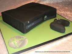 Xbox Cake. XBOX 360 Slim games console novelty birthday cake. Accompanied by an also cake made controller and the board decorated with the famous Xbox logo birthday message