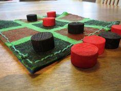 Risti-nolla -peli. Rajaukset teipin avulla. Sivussa pieni aukko, joten nappulat kulkevat pelin mukana.