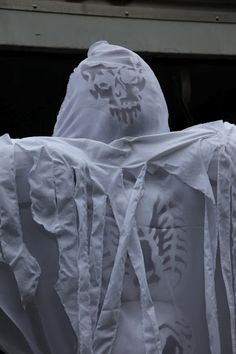 Once assembled, the scarecrows are draped with torn sheets.