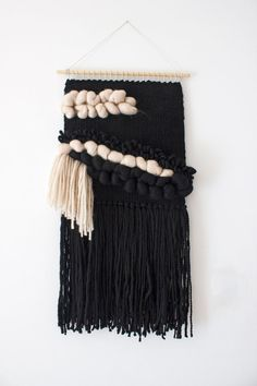 "Hand woven using a variety of weaving techniques to create a lovely piece of art for your walls.  With tonnes of texture, this unique wall hanging made with alpaca and wool yarns in black, black and nude/sand merino wool roving is the perfect statement piece for your walls.  Colours are true but please be aware that there may be differences between my monitor and yours.  Hung on a 40 cm (16"") wooden dowel, this weaving hangs 77 cm (30"") long from the dowel to end of fringe, and is 40 cm…"