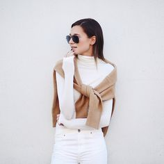 Take note: We Wore What styled a camel colored sweater over her white attire.