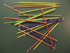 Pick up stix. My mom me taught me how to play this game. The game came in a long cylinder container.