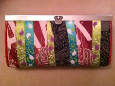 """my no-sew """"patch work"""" wallet.  I used a peel-and-stick adhesive to put on strips of a couple old t-shirts and ribbon."""
