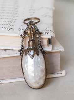 "Antique French Mother of Pearl Scent Bottle ♥ Charming antique mother of pearl scent bottle that would have been worn as one of the necessities chosen for a fashionable 19th century chatelaine. It has When closed the bottle is 2-3/4"" long and 1"" wide. The bottle is caged in a brass bezel decorated with a twisted rope design."