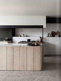 Modern kitchen interior with white tiled walls, marble tops and wooden island.