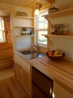 This tiny house kitchen includes a two burner cooktop, under counter refrigerator, and upper shelving.  Payette by Greenleaf Tiny Homes.
