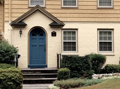 A saturated blue door keeps this two-toned house from fading into the landscape, but it still maintains a traditional feel. The paint color shown is Sherwin-Williams Regatta.