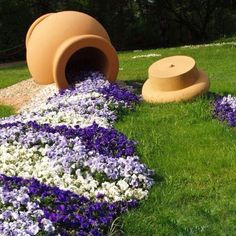 Spilling Flower Pot. Out of the mouth of the urn, white, lavender, and violet flowers spray out across the yard. The flowers are arranged in bands, somewhat like ripples.  http://blog.gardenloversclub.com/gardens/spilling-flower-planter-ideas/2/