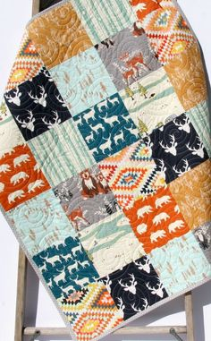 """Adorable modern boy quilt in navy, mint, gold, blue, and orange with bucks, deer, forest scenes, feathers, Aztec, wood grain, and a modern rustic theme throughout. You can choose the size baby (35""""x43"""