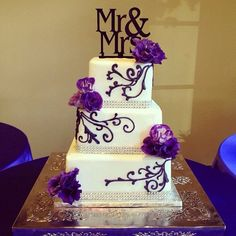 This 3 tier square cake has a smooth base and purple embellished swirls coming out of the matching purple fresh flowers. A plastic bling ribbon was used for the border on all 3 tiers ! This cake serves 100
