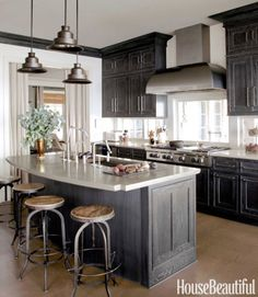 In a coastal kitchen inspired by sand and driftwood, the stained pine cabinets' color changes with the light, but the gray undertones consistently complement the iron pendants and the steel hood. Click through for more kitchen cabinet design ideas.