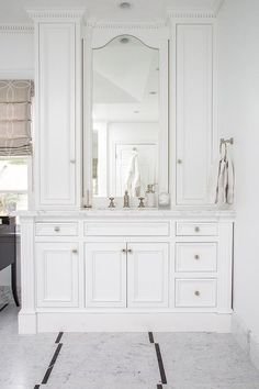 A built in washstand displays lots of drawer and cabinet storage space with oversized moldings and and nickel knobs.