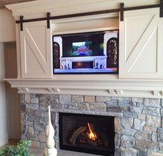 barn door hides tv over fireplace... brilliant!