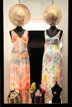 On the left wearing: 1970s tailor-made rayon dress with flowers print, 1950s coral and pearls necklace, 1970s Florentine straw hat.  Outfit on the right: 1970s Ken Scott rayon dress, 1950s pink hard stones necklace, 1970s Florentine straw hat. On the pedestal: 1980s Radà straw bag, 1980s Radà straw headband, 1960s coral earrings, 1980s rafia earrings, 1920s French pink and orange earrings, black pearls necklace, 1990s KJL sea star brooch.