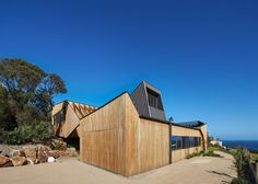 Angular volumes clad intimberand metal step down the side of a sloping site to formthishousenear Melbourne with ocean view.