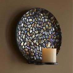 """Pebble glass mosaic plate glimmers with a mesmerizing, iridescent finish when lit by candlelight. Includes a metal sconce bracket for wall or table use. Sconce, or plate holds a round pillar, Escential jar, tealight, or large tealight, sold separately. Plate also holds a 3-wick. Includes hanging hardware. Assembled: 12 1/4"""" h, 6"""" d. Plate: 12"""" dia."""