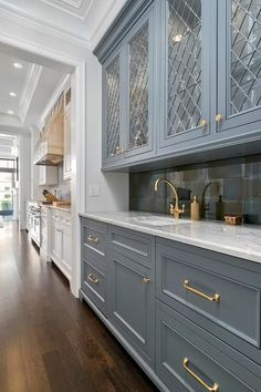 Gorgeous gray wet bar features gray cabinets painted Benjamin Moore Gunmetal and accented with gold pulls and a white quartzite countertop fitted with a rectangular sink and a gold gooseneck faucet positioned in front of smoke gray mirrored backsplash tiles lining upper cabinets finished with metal lattice doors.
