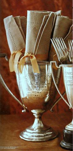 vintage trophies as napkin and fork holders. ideal and charming.