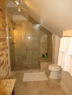 After: The shower with frameless door and river rock floor.